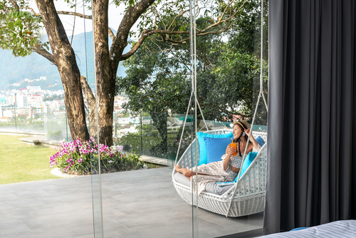 lady sitting outdoors photographed through frameless sliding doors