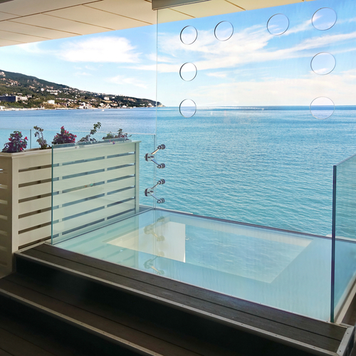 a beautiful view of sea photographed through frameless sliding glass doors
