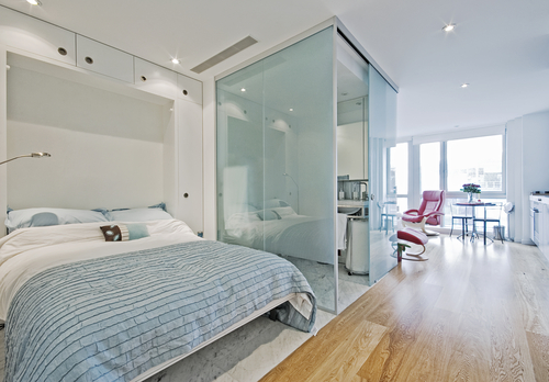 a light bedroom with frameless sliding doors